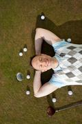 Man with balls and club lying on grass at golf course Stock Photos