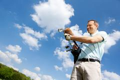 Man removing golf club against sky Stock Photos