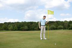Stock Photo of man putting flag in hole at golf course