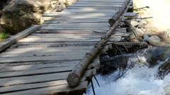 Wooden foot bridge over mountain river Stock Footage