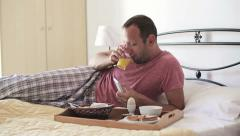 Stock Video Footage of Man with smartphone eating breakfast in bed HD