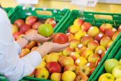 Shopper purchasing apples in a supermarket Stock Photos