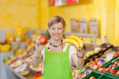 friendly saleswoman showing different fruits - stock photo