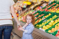 Cute little girl roaming in the supermarket Stock Photos