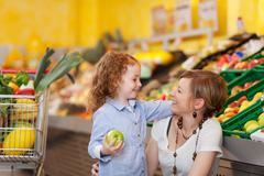 mother and daughter in the food department - stock photo