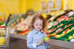 girl reading checklist while holding apple at grocery store - stock photo