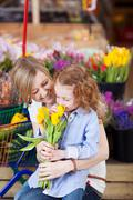 mother and daughter buying tulips - stock photo