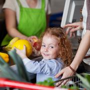 cute girl buying a melon in the supermarket - stock photo
