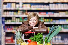 Woman with a shopping cart of fresh produce Stock Photos