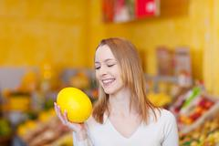 Cute young female choosing a melon to buy Stock Photos