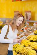 Nuori nainen ostaa tuoreita hedelmiä ja tuottaa Kuvituskuvat