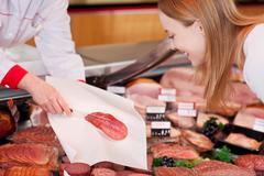 saleslady serving sliced salami - stock photo