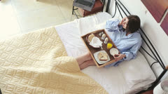 Woman in bed talking on cellphone during breakfast HD Stock Footage