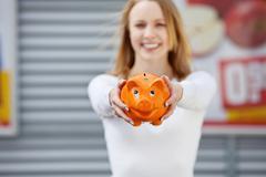beautiful young woman showing her piggy bank - stock photo