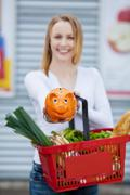 woman holding piggy bank and shopping basket - stock photo