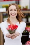 Attractive young woman showing a bunch of flowers Stock Photos