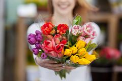 Woman showing a bunch of assorted flowers Stock Photos