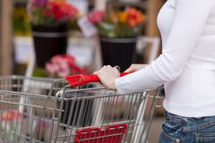 Woman pushing shopping cart in supermarket Stock Photos