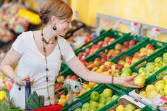 Woman choosing apples in grocery store Stock Photos