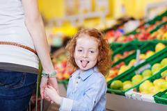 girl sticking out tongue while holding mother's hand in grocery - stock photo