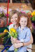 girl and mother holding flowers in supermarket - stock photo