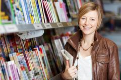 Woman holding newspaper in supermarket Stock Photos