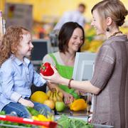 Woman giving capsicum to daughter at cash counter in supermarket Stock Photos