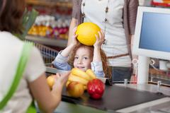girl giving muskmelon to cashier for billing at supermarket - stock photo