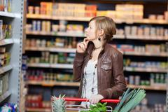 thoughtful woman looking at products in supermarket - stock photo