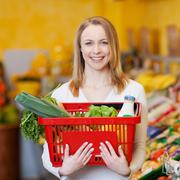 Beautiful woman carrying shopping basket in grocery store Stock Photos