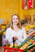 Kantava nainen ostoskorista ruokakauppaan Kuvituskuvat