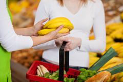 female worker assisting customer in purchasing bananas - stock photo