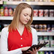 Saleswoman reading checklist on clipboard in grocery store Stock Photos