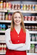 saleswoman with arms crossed standing in grocery store - stock photo