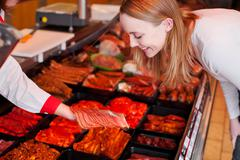 Woman looking at sliced meat on butcher hand at supermarket Stock Photos
