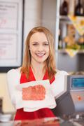 Female worker displaying sliced meat in grocery store Stock Photos