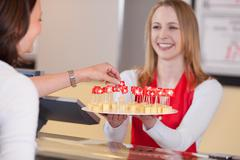 saleswoman offering cheese blocks with swiss flag to customer - stock photo