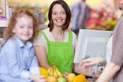 confident female cashier smiling at supermarket - stock photo