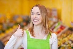 Female worker showing thumbsup gesture in grocery store Stock Photos