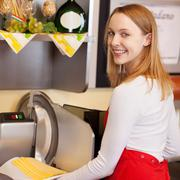 saleswoman holding sliced cheese while standing against machine - stock photo