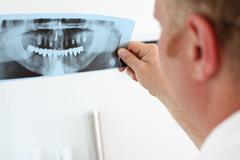 dentist looking at dental x-ray - stock photo