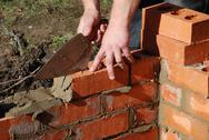 Stock Photo of bricklayer build house extension.