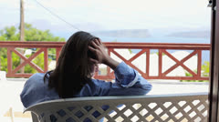 Sad woman sitting on terrace and drinking frappe HD Stock Footage