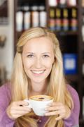Pretty woman holding cup of cappuccino Stock Photos