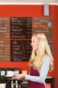 Young waitress serving coffee in cafe Stock Photos
