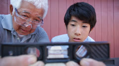 Asian Senior Man and Grandson Looking at Level Tool Stock Footage