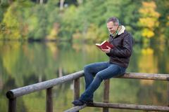 Man Reading Book While Sitting On Fence Against Lake Stock Photos