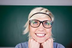 Funny blond woman laughing against chalkboard Stock Photos