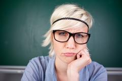 young woman contorting her face against chalkboard - stock photo