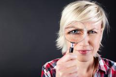blond woman with magnifying glass - stock photo
